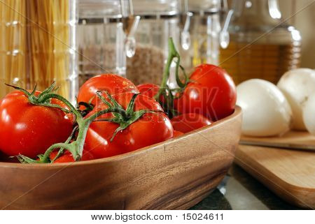 Freshly washed tomatoes in wooden bowl with onions, pasta, and glass canisters in the background.  Close-up with shallow dof and selective focus on closest tomato.