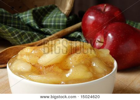 Cooked apples sprinkled with cinnamon.  Basket with green fabric, vintage wooden spoon and apples in the background.  Close-up with shallow dof.