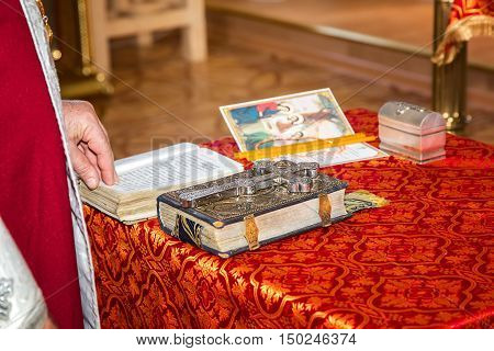 The priest reads the Bible. A large cross lies on the Bible on the table with a red tablecloth. At a ceremony in the Christian Church.