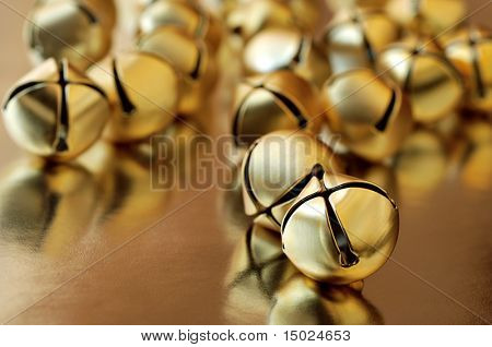 tiny gold jingle bells reflecting on metallic gold paper.  Macro with extremely shallow dof.  Selective focus on closest bell.