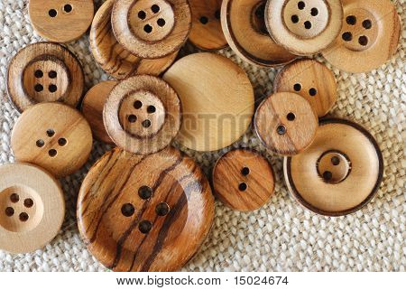 Vintage wooden buttons on handwoven cotton fabric.  Natural side lighting to emphasize textures.