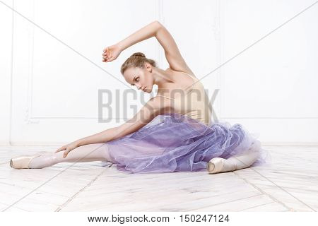 Beautiful Young Woman Ballerina Stretching Warming Up In White Interior