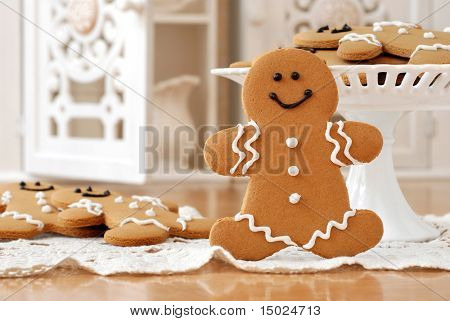 Smiling gingerbread man standing next to pedestal plate with additional cookies.  Ornate, cutwork cabinets in soft focus in the background.