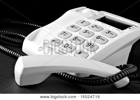 Telephone with receiver off the hook. Black and white macro image with shallow dof.  Desk surface has some visible texture.