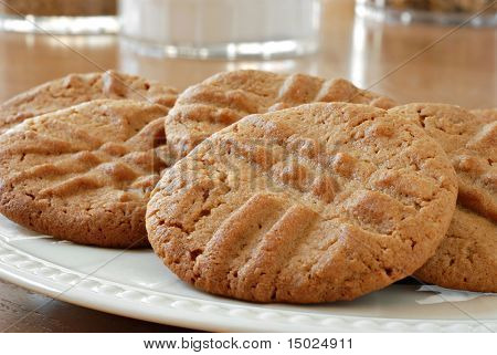 Freshly baked peanut butter cookies with canisters of baking ingredients in the background.  Macro with shallow dof.