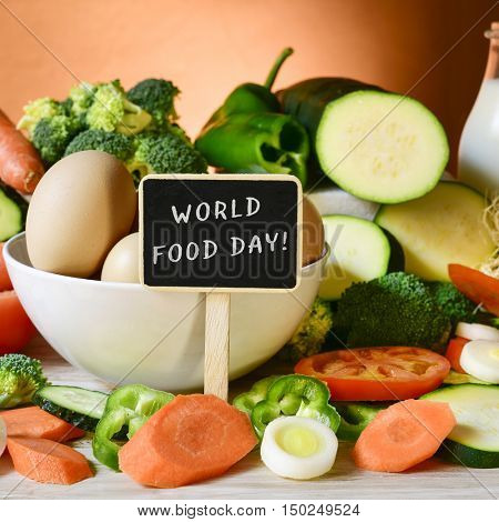 closeup of a chalkboard with the text world food day placed on a table fool of food, such as eggs, milk and pile of different raw vegetables