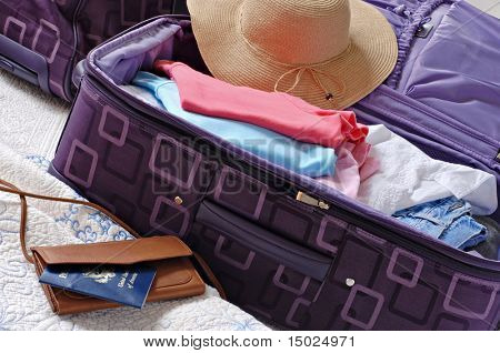 Modern luggage partially packed with colorful summer clothing.  US passport included in composition.