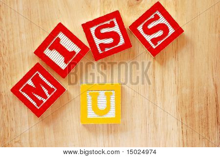 'Missing you' sentiment spelled out with alphabet blocks on wood grain background.