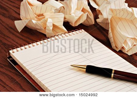 Blank notepad with ink pen on wooden desk.  Crumpled paper in soft focus in background - conceptual image for creative block.