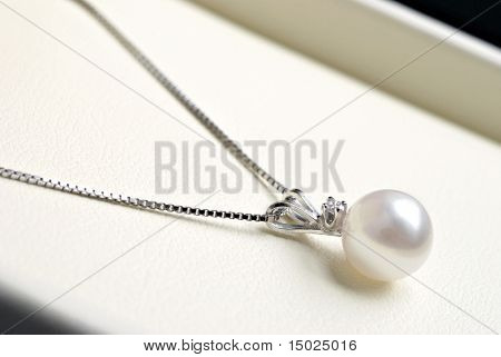 Elegant single pearl with diamond in white gold setting.  Macro of pendant in gift box.  Shallow dof.