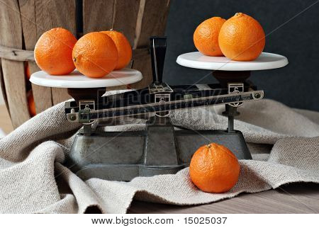 Classic still life of vintage kitchen scales with clementine oranges.  Antique fruit basket and handwoven fabric in soft focus in background.
