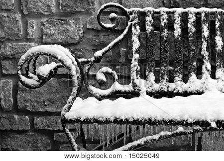 Black and white image of decorative wrought iron bench with snow and ice.