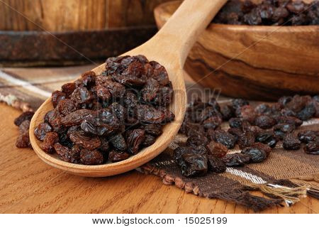 Raisin still life with wooden spoon and bowl. Rustic wooden bucket in soft focus as background.  Macro with shallow dof.