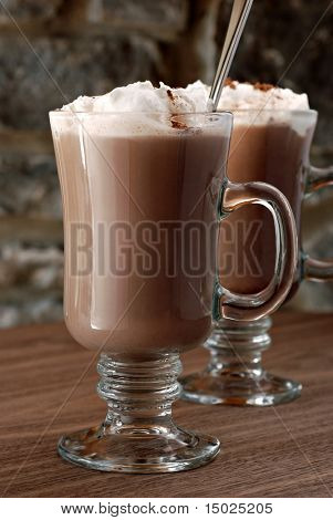 Heiße Schokolade oder Kaffee Latte im irischen Kaffeebecher mit Steinmauer im Hintergrund.  Makro mit extrem