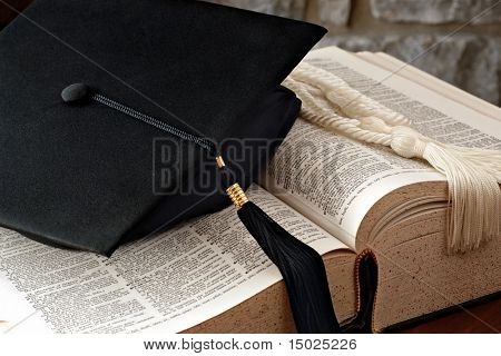"Graduation cap with tassel and honor cords lying on open dictionary.  Defined word in strongest focus is ""graduation"".  Macro with shallow dof."