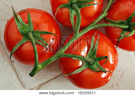 Vine of fresh ripe tomatoes on kitchen counter.  Macro showing details and water droplets.