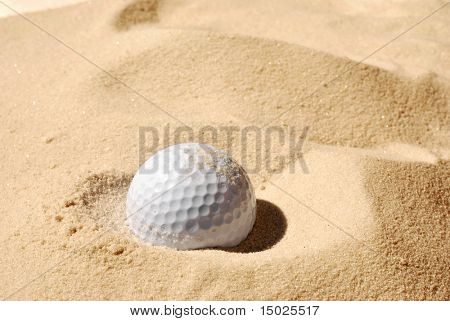 Sunlit golf ball with shadow in unraked sand trap.  Macro with shallow dof.