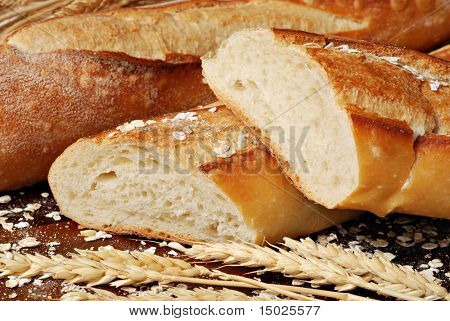 Freshly baked french baguettes with oats and wheat spikes.  Macro with shallow dof.