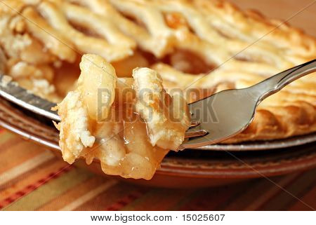 Bite of apple pie on fork with whole pie in soft focus in background.  Macro with extremely shallow dof.