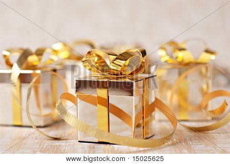 Soft focus holiday background with tiny sterling silver giftbox ornaments and gold ribbon.  Macro with extremely shallow dof.