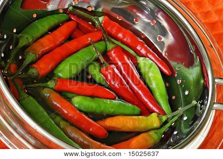 Colorful, freshly picked chili peppers in stainless steel colander with water.  Macro with shallow dof.