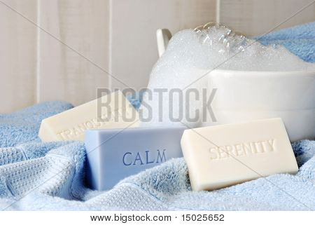 Soft blue and ivory embossed soaps on blue towel with small wash tub of bubbles in background.  Macro with shallow dof.