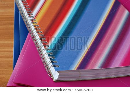 Colorful spiral notebook with matching folders on wood background.  Macro with shallow dof.