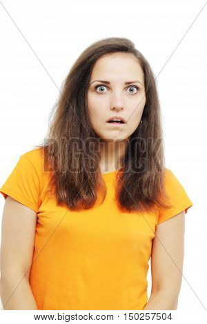 Close-up portrait of surprised beautiful girl open-mouthed. Over white background. Surprised, crazy girl in an orange T-shirt. Brunette girl's reaction.