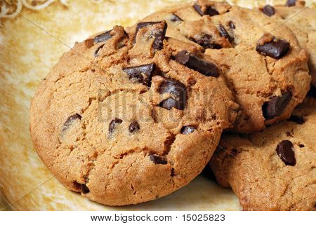 Freshly baked chocolate chip cookies on decorative plate.  Macro with shallow dof.