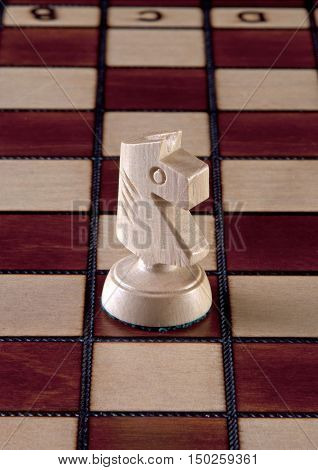 White knight chess piece isolated on a chessboard