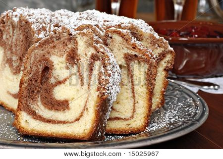 Freshly baked cinnamon swirl coffee cake with cherry topping and tableware in background.  Closeup with shallow dof.