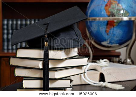 Graduation cap on stack of books with globe and bookshelves in soft focus in background.  Close-up with shallow dof.