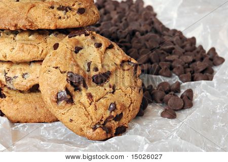 Stack of freshly baked chocolate chip cookies on crumpled wax paper with extra chocolate chips in background.  Macro with shallow dof.