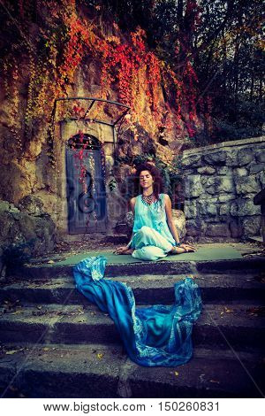 young woman in yoga meditation position on old stairs and stone wall autumn day