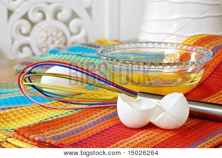 Colorful egg whisk with bowl of fresh eggs and eggshells on brightly colored dish towels.  Close-up with shallow dof.