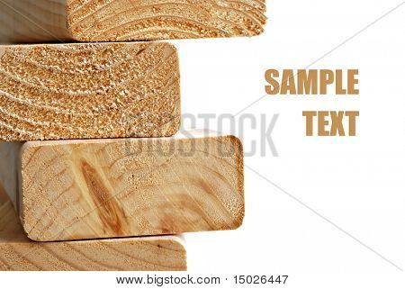 Stack of wooden 2X4s on white background with copy space.