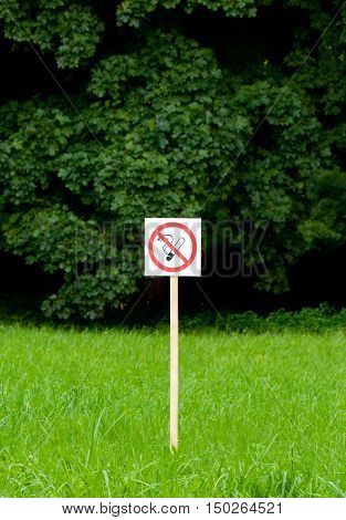 No smoking sign in the park on bright green trees and grass background