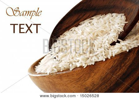Arroz crudo en recipiente de madera con cuchara sobre fondo blanco con espacio de copia.  Macro con poca profundidad dof