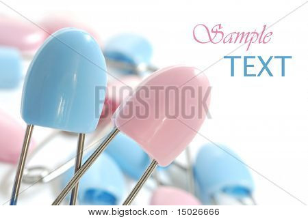 Blue and pink diaper pins on white background with copy space.  Macro with extremely shallow dof.