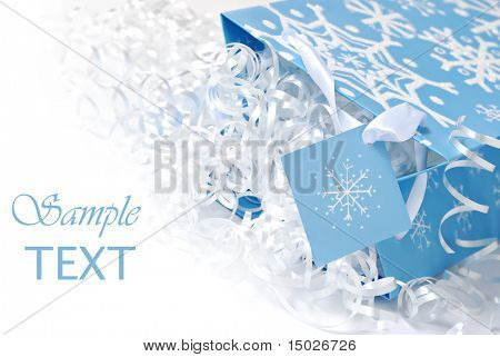 Snowflake gift bag with shiny curling ribbon on white background with copy space.  Macro with shallow dof.