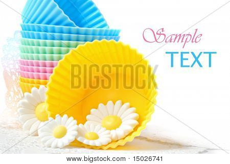 Colorful silicone baking cups with daisies made of cake icing on white background with copy space.  Macro with shallow dof.