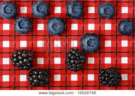 Colorful red and white napkin with fresh berries arranged to symbolize playing a game of checkers.