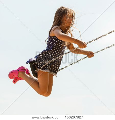 Girl Swinging On Swing-set.