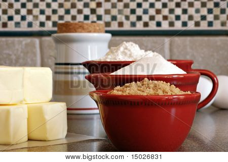 Ceramic measuring cups filled with flour and sugar along with eggs and butter on kitchen counter.  Macro with shallow dof.
