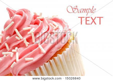 Cupcake with swirls of creamy strawberry frosting on white background with copy space.  Macro with shallow dof.