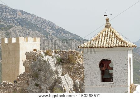 foreground of castle tower and bell tower on the village of guadalest in the province of alicante spain