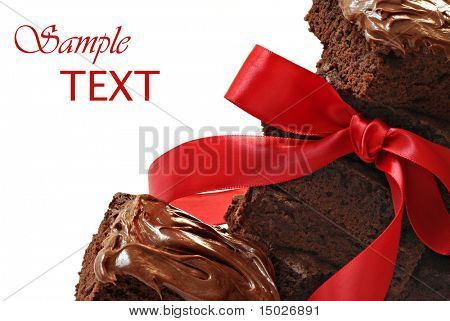 Gift for chocolate lovers.  Freshly baked brownies with red satin ribbon on white background with copy space.  Macro with shallow dof.