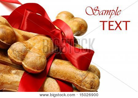 Healthy dog treats with red satin ribbon on white background with copy space.  Macro with shallow dof.