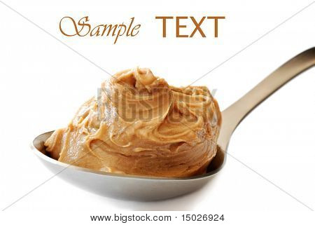 Peanut butter in large serving spoon on white background with copy space.  Macro with shallow dof.