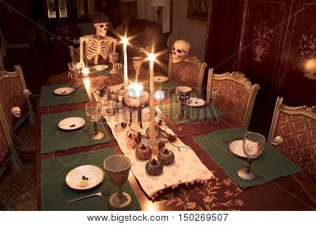 Skeleton family gathered for a Halloween dinner celebrating the holiday at a formal dining table